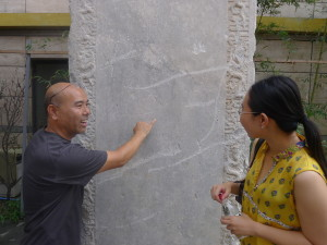 Museum Curator Mr Yuan Qiulai shows the names of the patrons who helped fund the rebuilding over the past 5 centuries